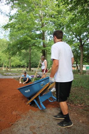 A male student dumps a wheelbarrow load of dirt onto the path where two female students are working.