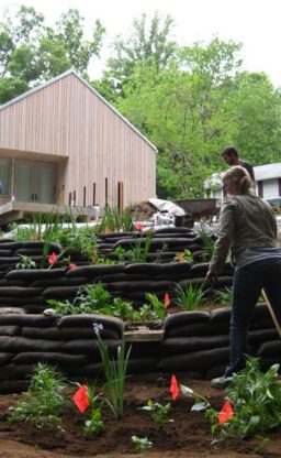 A group works in the terraced garden adjacent to the house.