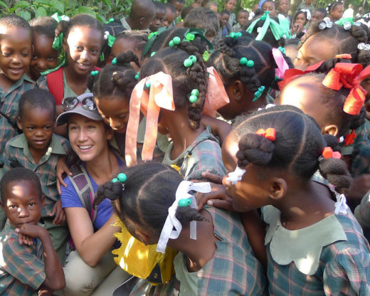 A large group of Haitian children in school uniforms surround a female University of Tennessee student.