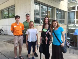 A family gathered outside of the Art + Architecture building